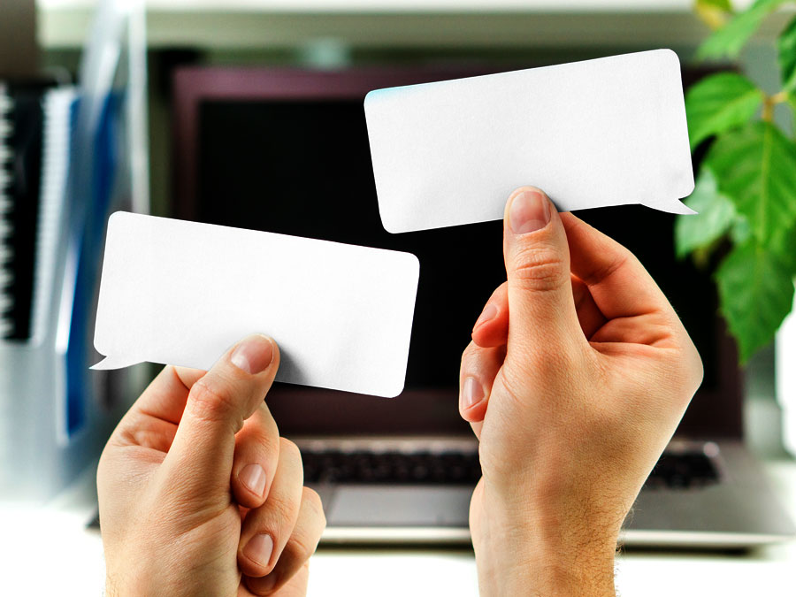 hands holding word balloons by laptop showing outsourcing live chat support