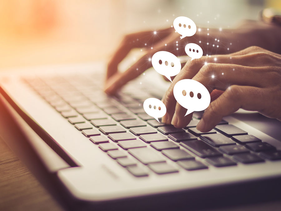 hands outsourcing live chat support agent typing on keyword with virtual word balloons