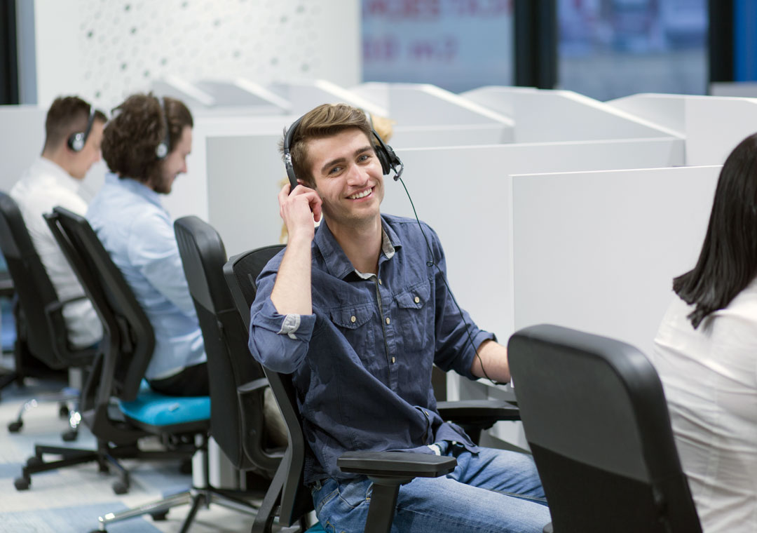 smiling customer care agent with call center team