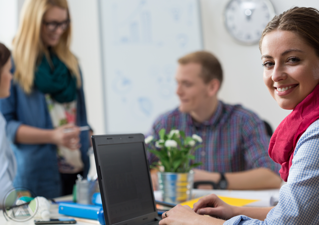 smiling-female-employee-on-laptop-with-chatting-coworkers