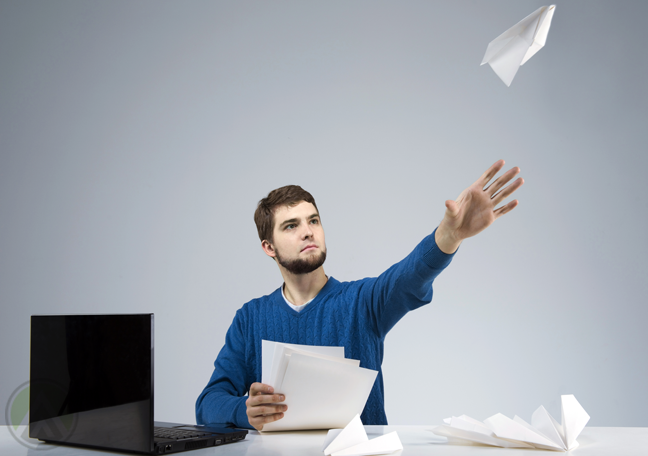 bearded-employee-flying-paper-planes-by-laptop