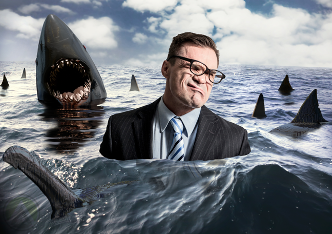 businessman-submerged-in-the-ocean-surrounded-by-sharks