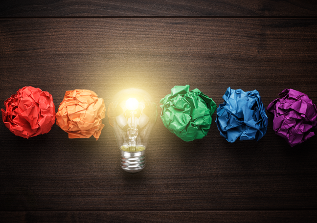 colorful-crumpled-paper-with-lit-light-bulb-in-dark