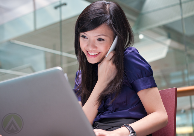 female-executive-in-phone-call-using-laptop