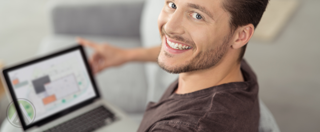smiling-man-sitting-on-couch-at-home-with-open-laptop