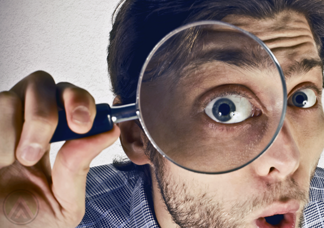surprised-male-business-executive-looking-through-magnifying-lence
