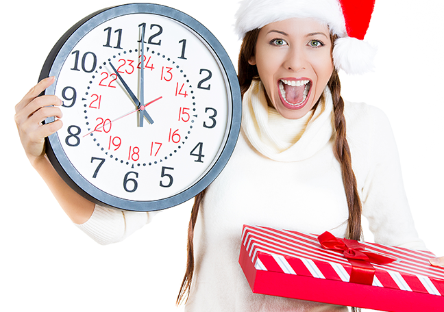 excited-female-wearing-santa-hat-holding-clock-and-gift