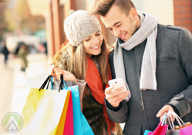 smiling-polish-poland-couple-with-shopping-bags-using-smartphone