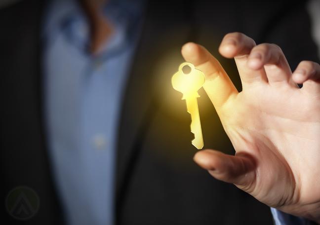 businessman-in-the-dark-holding-glowing-key