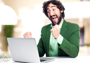excited-bearded-man-in-green-coat-looking-at-laptop