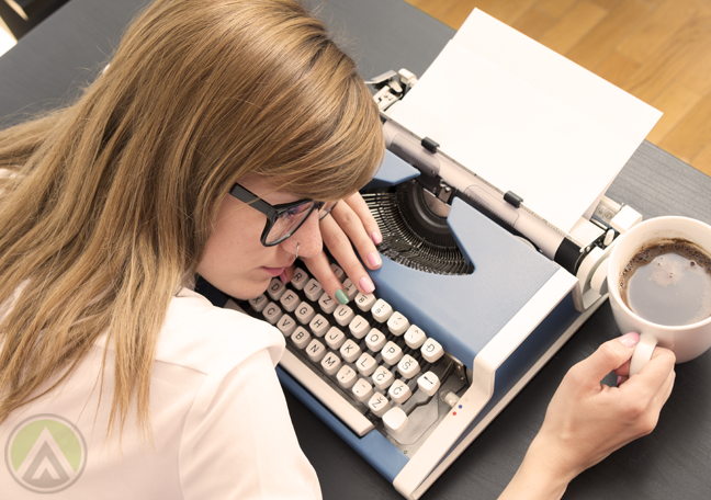 female-writer-in-glasses-resting-on-typewriter-holding-coffee-mug