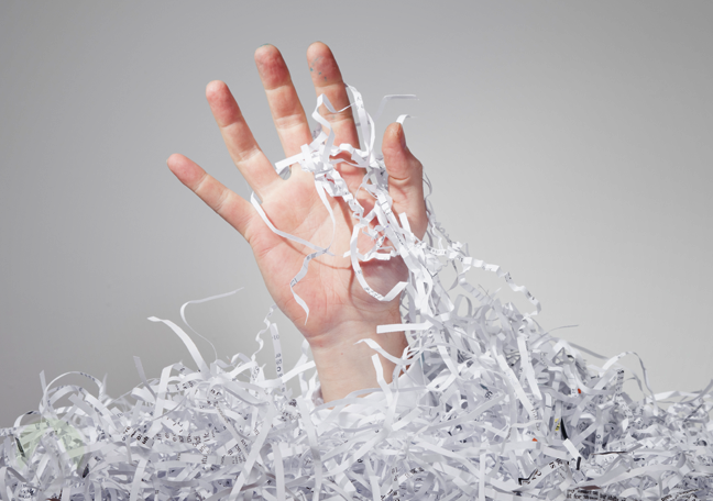 man-drowning-in-shredded-paper
