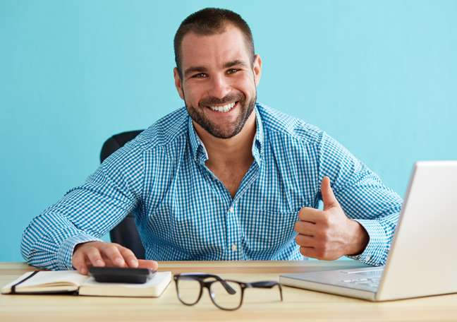 bearded-businessman-giving-thumbs-up-by-laptop