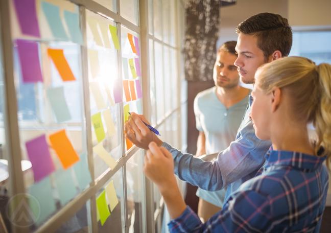 business-creative-team-writing-on-postit-notes-on-window