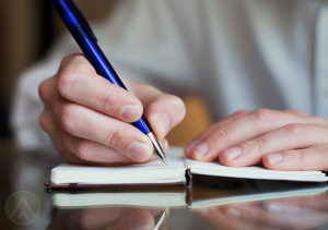 close-up-hand-holding-ball-point-pen-writing-on-notebook