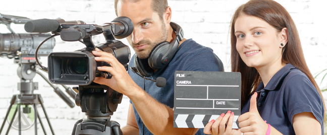 director-with-video-camera-assistant-holding-clapper