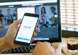 hand-holding-iphone-smartphone-with-LinkedIn-mobile-app-background-laptop