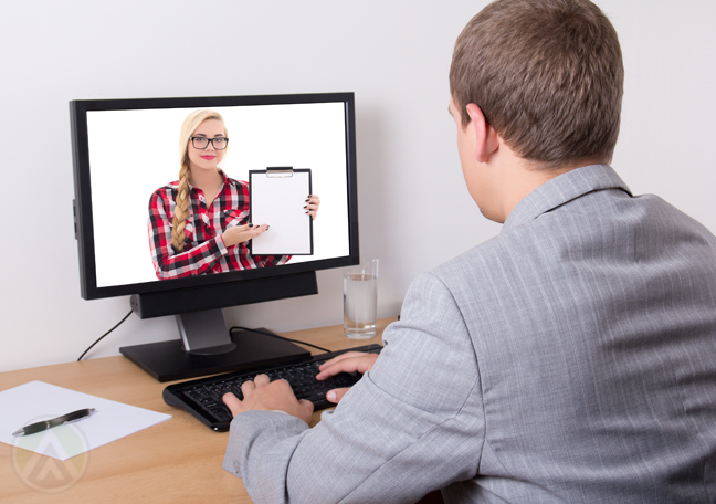 man-using-computer-with-woman-holding-clipboard-on-monitor-screen