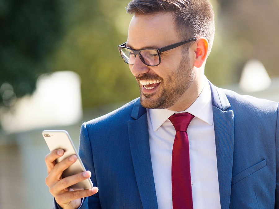 smiling man looking at ecommerce site customer support on phone
