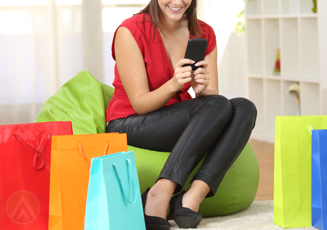woman-wearing-red-shirt-using-smartphone-sitting-on-green-beanbag-with-shopping-bags