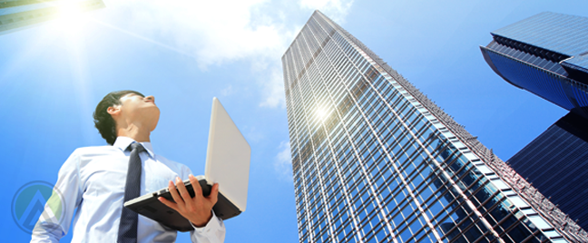 young-asian-male-businessman-holding-laptop-outdoors-looking-up-at-building