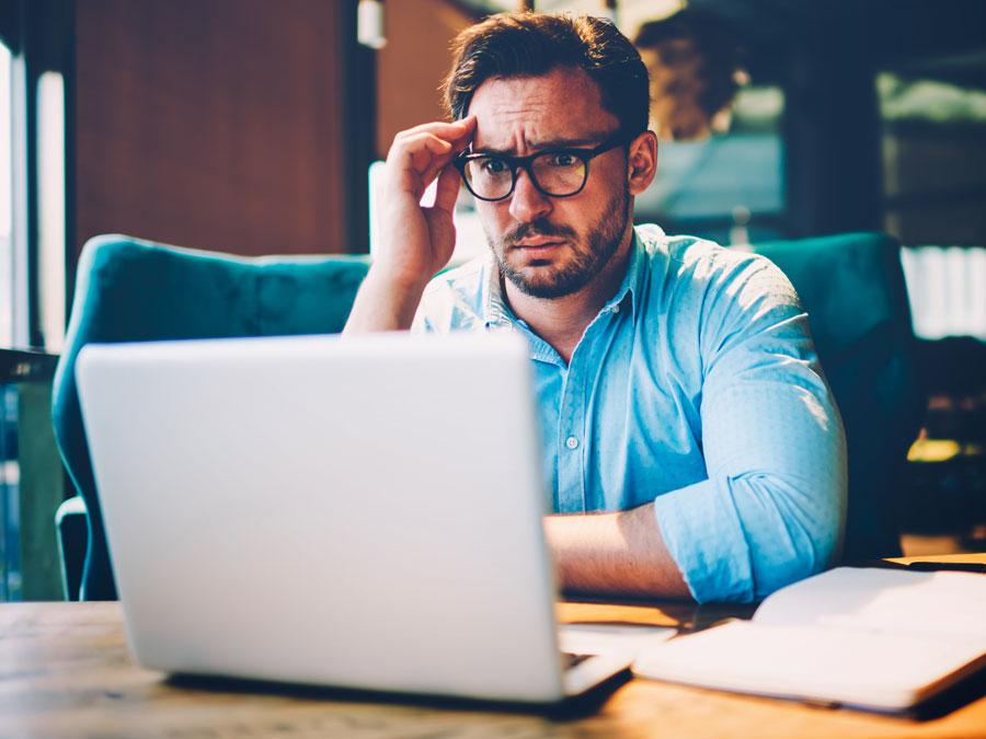 confused thinking businessman focused on laptop