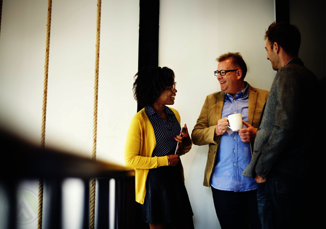 diverse-business-team-chatting-in-office-hallway