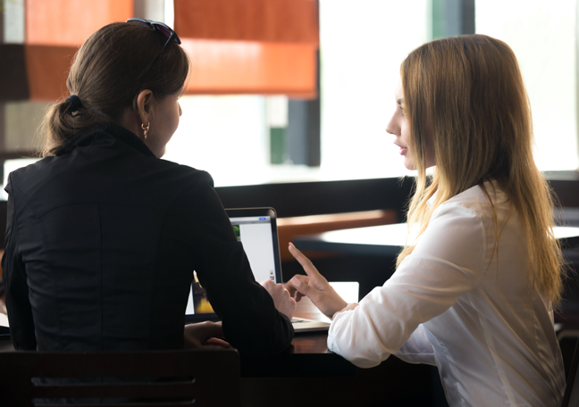 female-coworkers-chatting-by-laptop