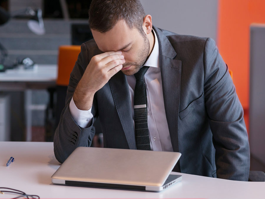 frustrated businessman with headache by laptop