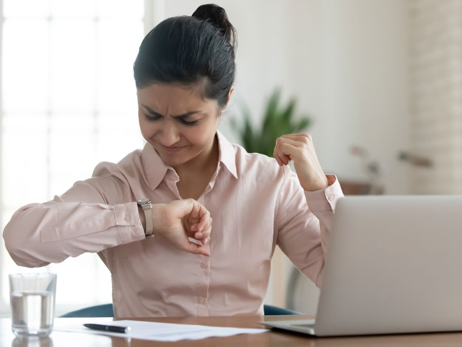 stressed woman using laptop looking at wrist watch