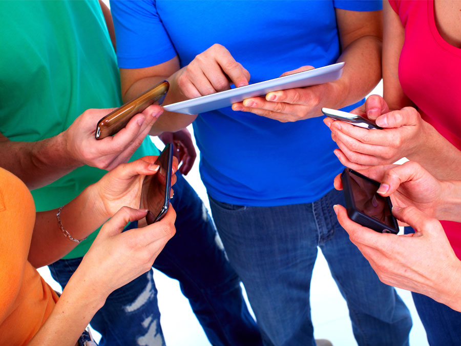 friends in colorful clothes using smartphone tablets