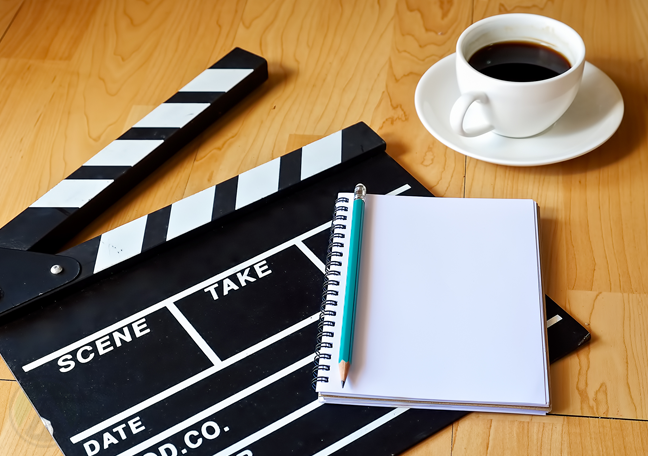 movie-clapper-on-the-floor-with-pen-and-notebook-and-coffee