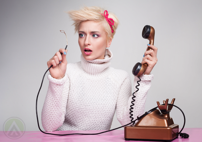 shocked-woman-holding-telephone-looking-at-disconnected-phone-cable