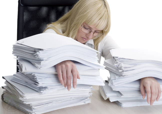 female-business-executive-with-hands-trapped-under-piles-of-paper