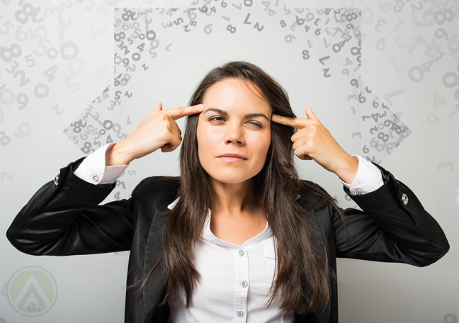 female-business-executive-with-headache-surrounded-by-numbers