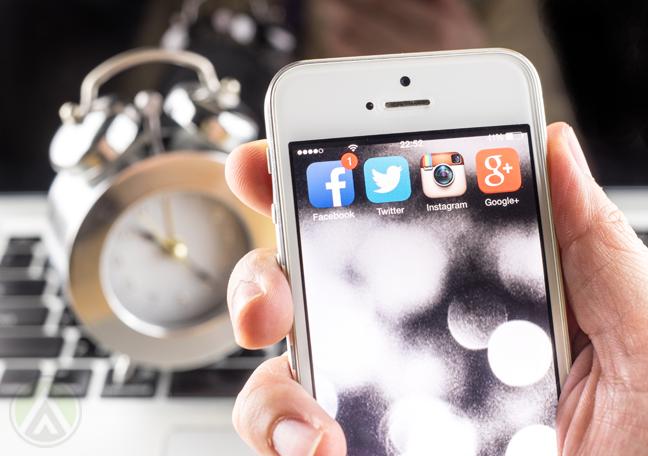 hand-holding-smartphone-near-keyboard-alarm-clock