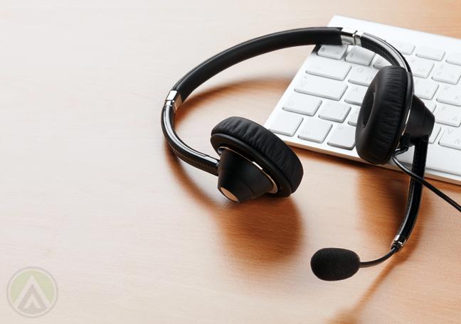 unused-call-center-headphones-on-computer-keyboard-on-table