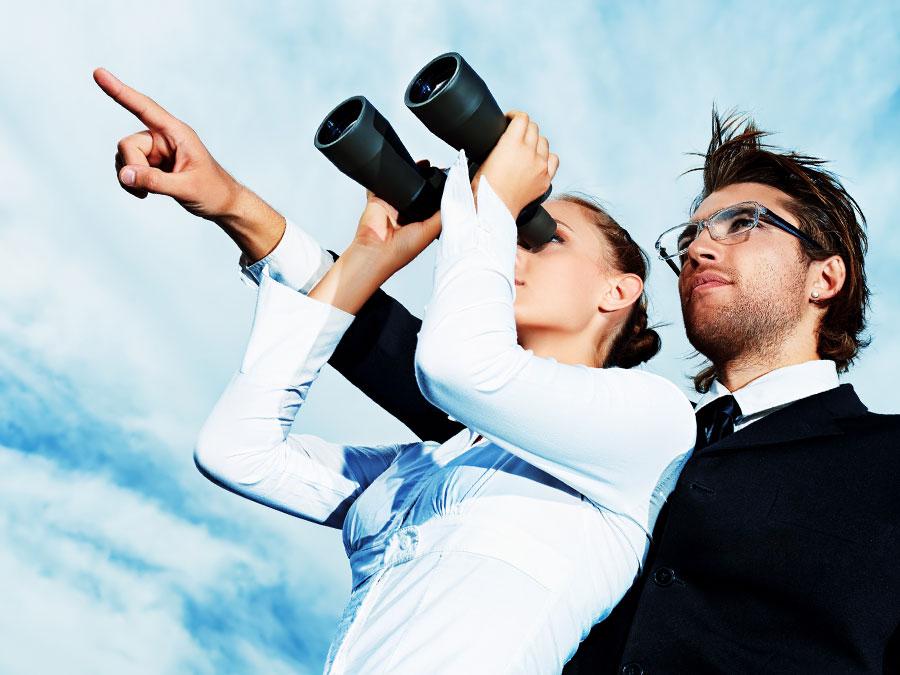 business partners looking through binoculars