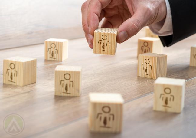 businessman-hand-holding-wooden-blocks-human-figures