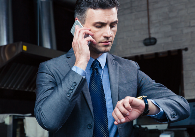 businessman-in-a-phonceall-looking-at-wrist-watch