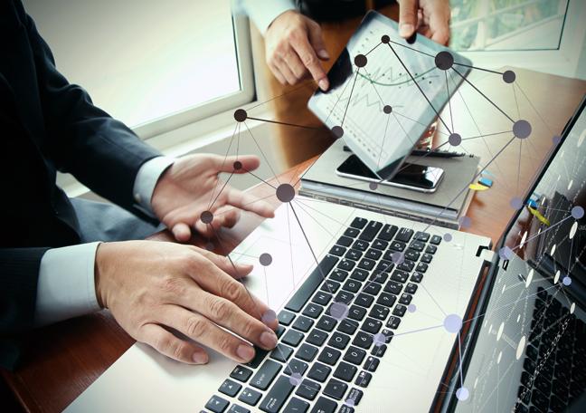 businessman-using-laptop-employee-handing-tablet
