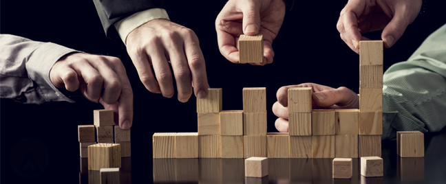 businessmen-hands-building-towers-wooden-blocks