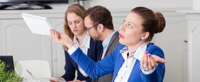 businesswoman-in-blue-giving-up-throwing-arms-holding-notebook-coworkers-workign-in-back