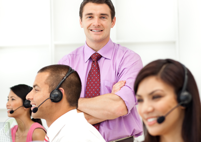 call center manager standing behind seated customer support agents