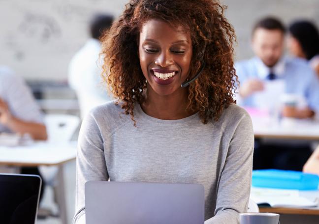 female customer service representative in a call using laptop