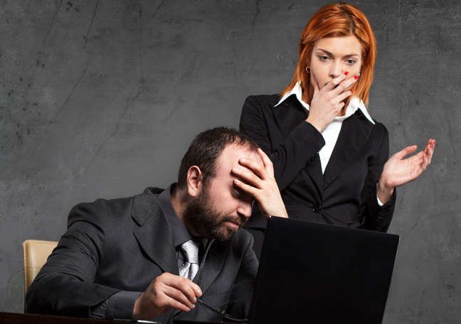 problematic-businessman-looking-at-laptop-shocked-female-coworker