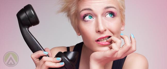 undecided-woman-holding-landline-phone-biting-fingernail-2