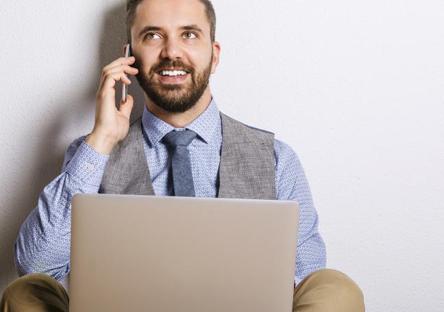 bearded businessman sitting on floor working on laptop
