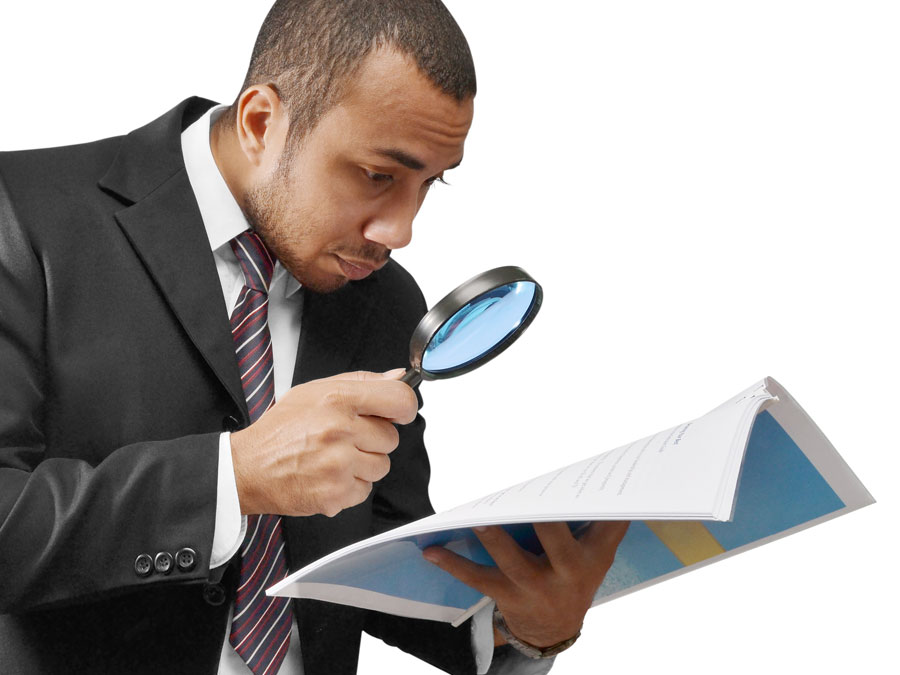 businessman looking at reports with magnifying lens