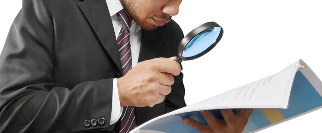 businessman using magnifying lens analyzing printed document